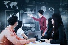 Geschäftsmann, der Finanzdiagramme in der Sitzung darstellt Stockbilder