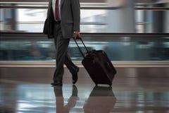 Geschäftsmann, der in Flughafen mit Koffer geht stockfotografie