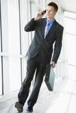 Geschäftsmann, der in Flur unter Verwendung des Handys geht Lizenzfreie Stockfotografie