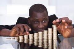 Geschäftsmann, der in Folge Münzen stapelt Stockbild