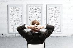 Geschäftsmann, der Formeln auf Schreibtisch schaut Stockbild