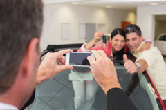 Geschäftsmann, der Foto der Paare in ihrem Neuwagen macht Lizenzfreie Stockfotos