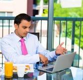 Geschäftsmann, der Frühstück und das Arbeiten isst lizenzfreies stockfoto