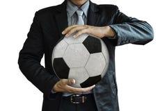 Geschäftsmann, der Fußball auf Weiß hält Stockbilder