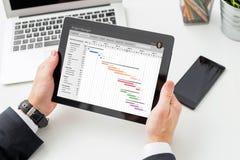 Geschäftsmann, der Gantt-Diagramm auf Tablet-Computer betrachtet Lizenzfreie Stockfotografie