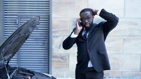 Geschäftsmann, der gebrochenes Auto mit der offenen Haube, sprechend über Telefon, Zusammenbruch bereitsteht lizenzfreies stockbild