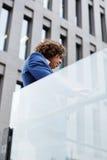 Geschäftsmann, der gegen Bürogebäude unter Verwendung einer digitalen Tablette steht Stockfotografie