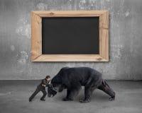 Geschäftsmann, der gegen schwarzen Bären mit leerer Tafel kämpft Lizenzfreie Stockfotos