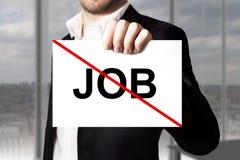Geschäftsmann, der gekreuztes heraus arbeitsloses des Zeichens Job hält Stockbild