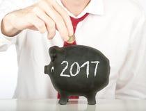 Geschäftsmann, der Geld auf eine piggy Querneigung steckt Stockbilder
