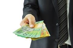 Geschäftsmann, der geld- australische Dollar gibt Lizenzfreie Stockfotografie