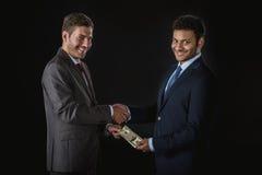 Geschäftsmann, der Geld gibt und den Teilhaber lokalisiert auf Schwarzem besticht Stockfotografie