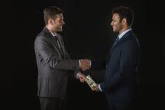 Geschäftsmann, der Geld gibt und den Teilhaber lokalisiert auf Schwarzem besticht Lizenzfreie Stockfotografie