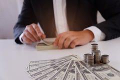 Geschäftsmann, der Geld mit Münzen und Geld über dem Schreibtisch zählt stockbilder