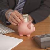 Geschäftsmann, der Geld in Piggy Querneigung einsetzt Lizenzfreies Stockfoto