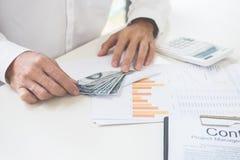Geschäftsmann, der Geld an der TabellenBilanzauffassung zählt stockbilder