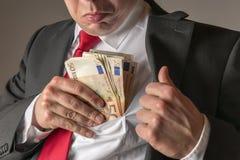 Geschäftsmann, der Geld in Tasche einsetzt Lizenzfreie Stockbilder