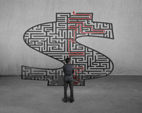 Geschäftsmann, der Geldformlabyrinth mit Lösung gegenüberstellt Lizenzfreies Stockfoto