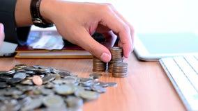 Geschäftsmann, der Geldmünzen und -input zählt, um auf Tabelle zu stapeln stock video footage