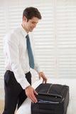 Geschäftsmann, der Gepäck an einem Hotelschlafzimmer auspackt Lizenzfreies Stockbild