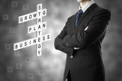 Geschäftsmann, der Geschäftskonzept durch Kreuzworträtsel schaut Stockfoto