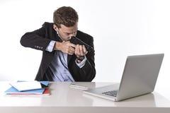 Geschäftsmann, der Gewehr auf Computer im Überlastungs- und Überstundenarbeitkonzept zeigt stockfotografie