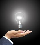Geschäftsmann, der Glühlampe anhält Lizenzfreies Stockfoto