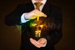 Geschäftsmann, der Glühlampe anhält Stockfotografie