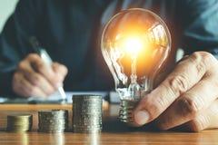 Geschäftsmann, der Glühlampe auf dem Schreibtisch im Büro und im writin hält Stockbilder