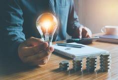 Geschäftsmann, der Glühlampe auf Schreibtisch im Büro hält und Ca setzt Stockfotos
