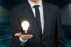 Geschäftsmann, der Glühlampe hält Lizenzfreie Stockbilder
