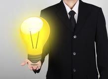 Geschäftsmann der Glühlampe an Hand Stockbilder