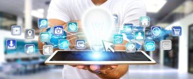 Geschäftsmann, der Glühlampe mit digitalen Ikonen hält Stockbilder