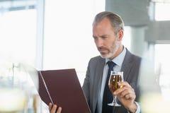 Geschäftsmann, der Glas Bier hält und Menü betrachtet stockbilder