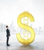 Geschäftsmann, der goldenen Dollar betrachtet Lizenzfreies Stockfoto