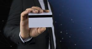 Geschäftsmann, der Goldkreditkarte hält Stockbild