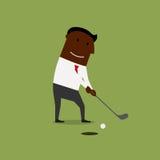 Geschäftsmann, der Golf am grünen Feld spielt Stockfotografie