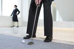 Geschäftsmann, der Golfball setzt. Stockfoto
