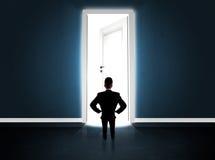 Geschäftsmann, der große helle geöffnete Tür betrachtet Stockfotos