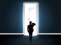 Geschäftsmann, der große helle geöffnete Tür betrachtet Lizenzfreie Stockfotos