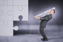 Geschäftsmann, der großes Puzzlespielstück hält lizenzfreie stockfotografie