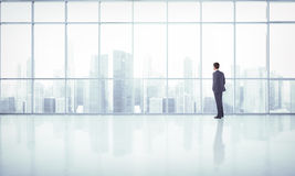 Geschäftsmann, der Großstadt durch Fenster betrachtet Stockbild