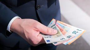 Geschäftsmann, der in der Hand Bargeld hält Stockfotos
