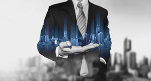 Geschäftsmann, der an Hand blaues modernes Gebäudehologramm, mit Schwarzweiss-Stadthintergrund hält lizenzfreie stockbilder