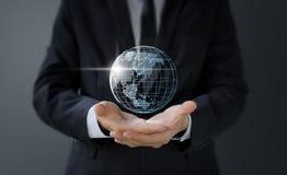 Geschäftsmann, der in der Hand digital erzeugte Weltkarte hält stockbild