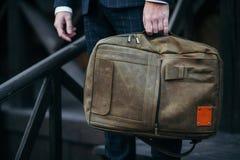 Geschäftsmann, der in der Hand einen Aktenkoffer im Vertrauen arbeitet steht und hält lizenzfreie stockfotografie