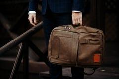 Geschäftsmann, der in der Hand einen Aktenkoffer im Vertrauen arbeitet steht und hält Stockfotos