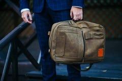 Geschäftsmann, der in der Hand einen Aktenkoffer im Vertrauen arbeitet steht und hält Stockfotografie