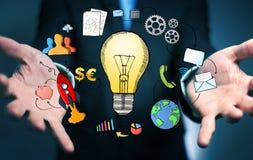 Geschäftsmann, der Hand gezeichnete Glühlampen- und Multimediaikonen hält Stockbild