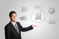 Geschäftsmann, der Hand gezeichnete Skizzendiagramme und -diagramme darstellt Lizenzfreie Stockbilder